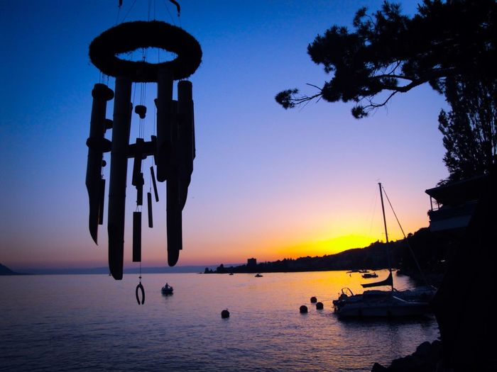 Silhouette wind chime hanging by lake against sky during sunset