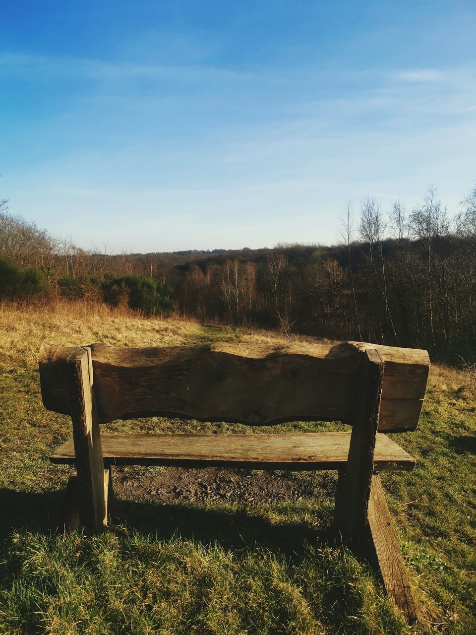 BENCH ON FIELD AGAINST SKY