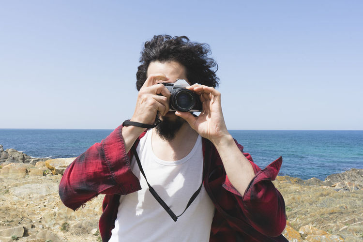 Man photographing on beach against clear sky