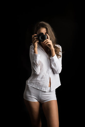 One Person Studio Shot Indoors  Young Adult Black Background Three Quarter Length Women Standing Portrait Front View Photographing Adult Hair Activity Photography Themes Casual Clothing Holding Camera - Photographic Equipment Hairstyle Beautiful Woman Photographer Shorts Obscured Face