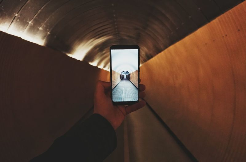 Man holding mobile phone in tunnel