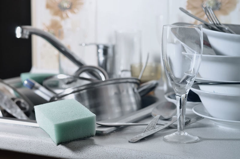 Kitchen utensils and cleaning sponge in sink