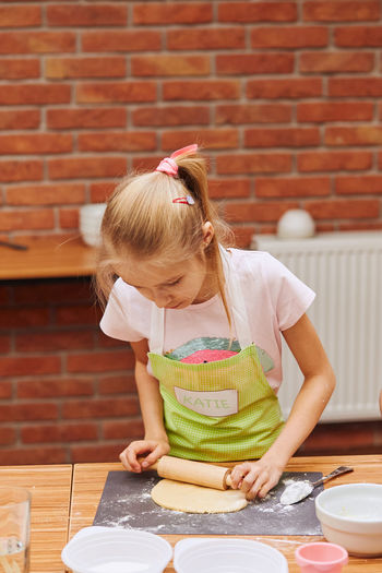 Girl rolling dough on table at home