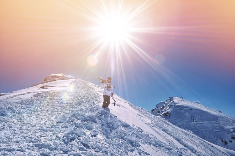 Hiker Walking On Snowcapped Mountains Against Sky During Sunny Day