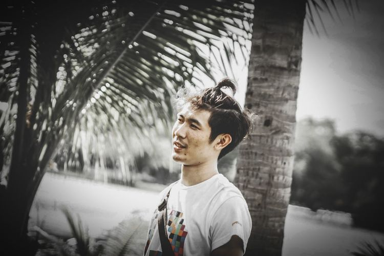 Portrait of young man standing by palm trees