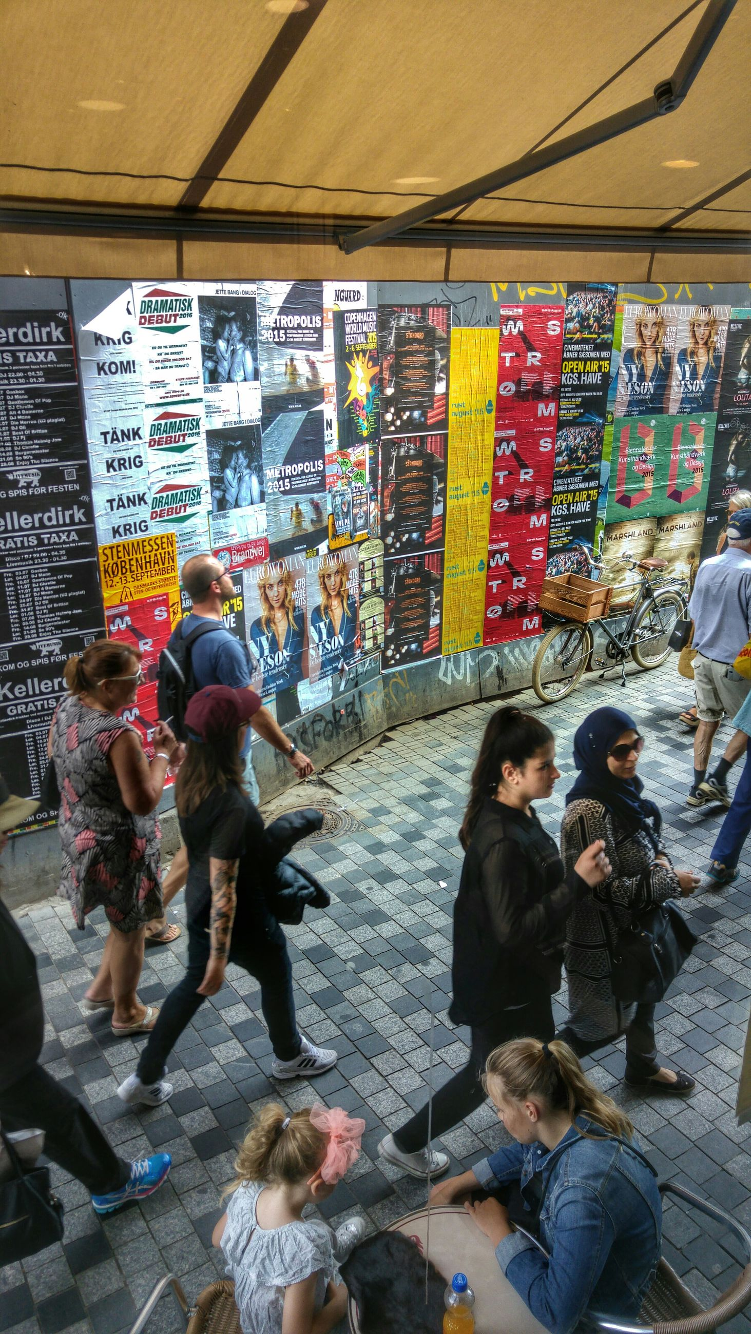 text, lifestyles, men, person, leisure activity, communication, indoors, graffiti, western script, large group of people, wall - building feature, casual clothing, non-western script, full length, store, multi colored, standing, street, transportation