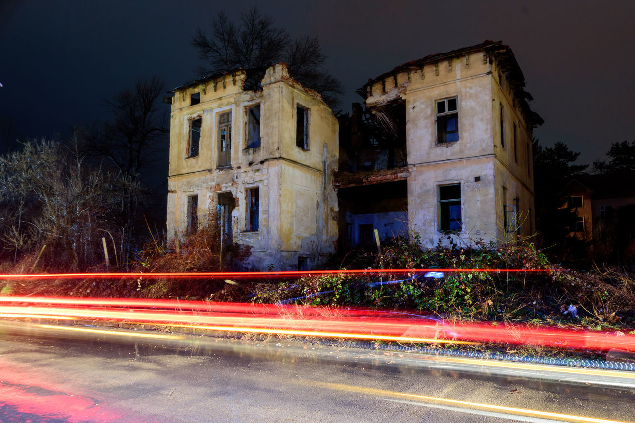 long exposure, light trail, motion, night, speed, building exterior, architecture, road, blurred motion, outdoors, illuminated, built structure, no people, tree, sky