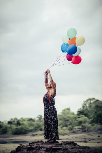 Full Length Of Woman Holding Balloons While Standing Against Sky