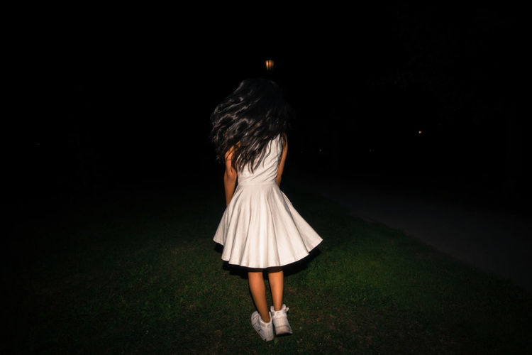 Rear View Of Girl Wearing Dress On Field At Night