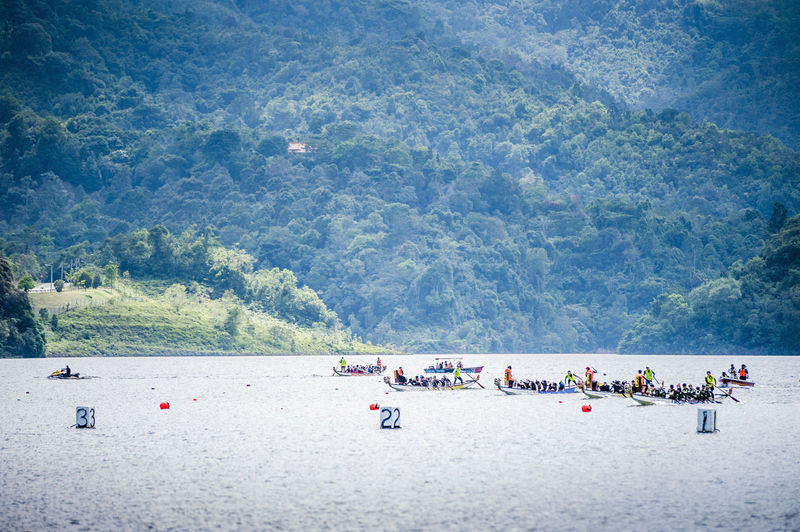 Dragon boat race in river against mountain