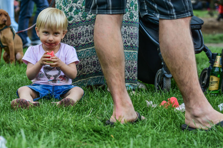 Bonding Casual Clothing Child Childhood Day Food Food And Drink Front View Grass Leisure Activity Lifestyles Low Section Men Nature Outdoors People Plant Shorts Sitting Togetherness Two People