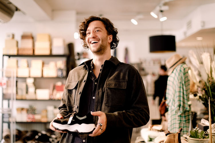 Portrait of a smiling young man standing in store