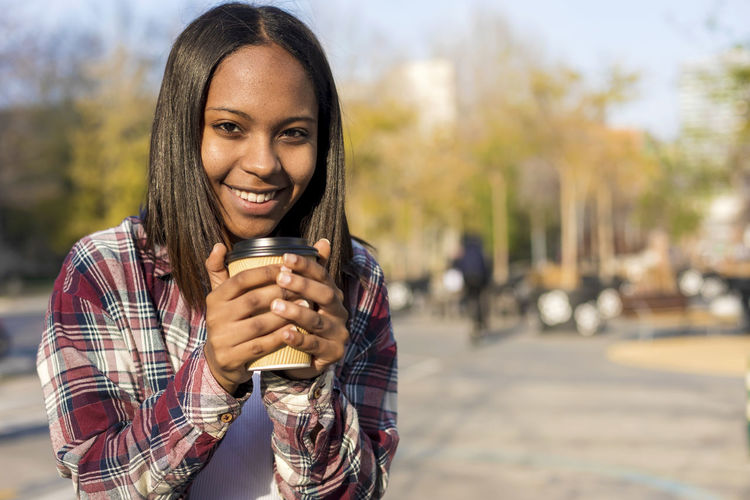 Young african american woman standing in city street while holding a take away coffee and looking camera in a sunny day Drink Smiling Portrait One Person Refreshment Looking At Camera Young Adult Drinking Holding Happiness Food And Drink Adult City Focus On Foreground Front View Emotion Coffee - Drink Cup Disposable Hair Hairstyle Beautiful Woman Glass Take Away Relaxing Sitting Laugh Laughing Outdoors Sunny Daylight