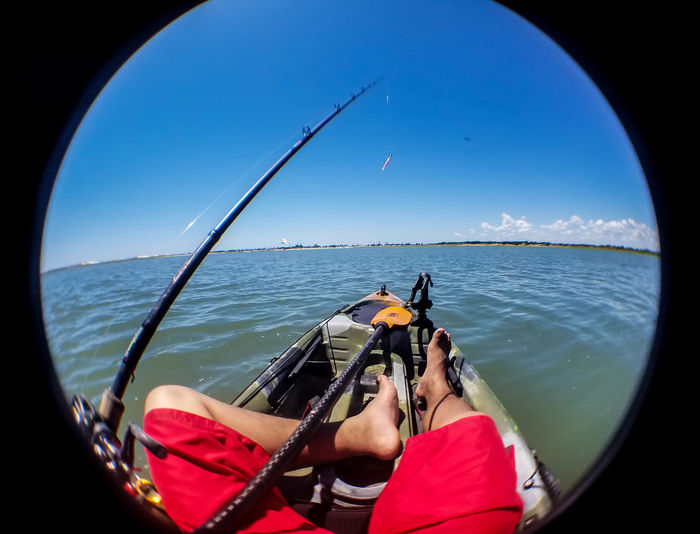 Low section of man relaxing in boat while fishing against clear sky