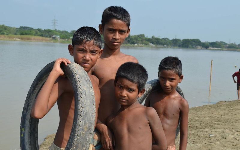Children Sibling Children Cloud Four Sky Riverside River Playing Childhood Children Photography Rural Life Shirtless Boys Real People Leisure Activity Elementary Age Water Portrait Lifestyles Outdoors Looking At Camera Togetherness Mature Men Day Standing Nature Son Vacations Bonding Men Young Adult Mammal