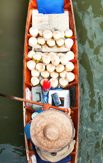 Directly above shot of woman with fruits on boat sailing in river