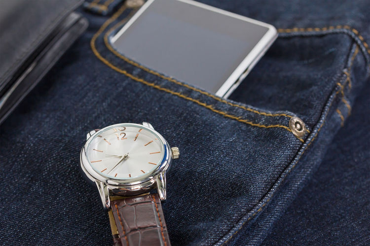 Close-up of watch and mobile phone on denim jeans