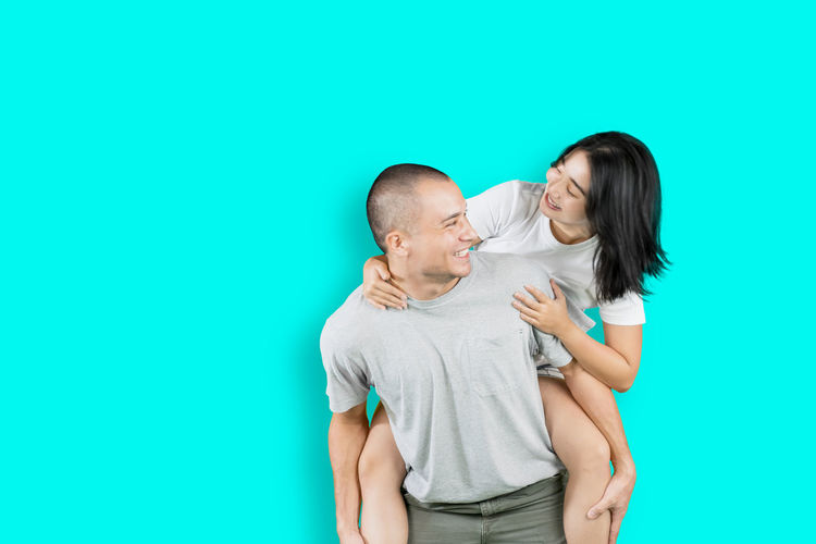 Friends standing against blue background
