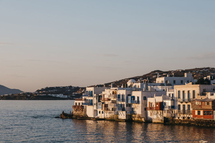 Sunset over the colourful old seaside houses in little venice, mykonos, greece.