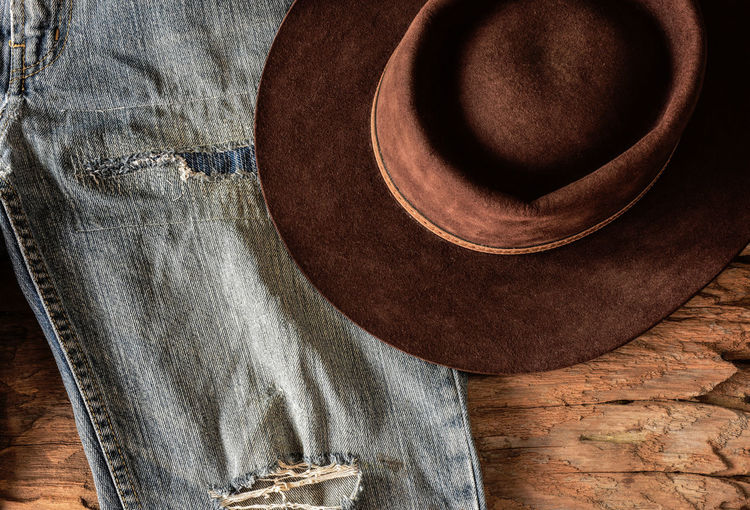 Faded jeans and felt hat on wood background. Patched and worn out blue jeans and cow boy hat. Classic Patch Ranch Life Rodeo Vintage Style Blue Jeans Country Style Cowboy Hat Denim Faded Jeans Felt Hat Hat High Angle View Indoors  Jeans Leather Rustic Style Still Life Stitches Textile Tough Wild West Wood - Material