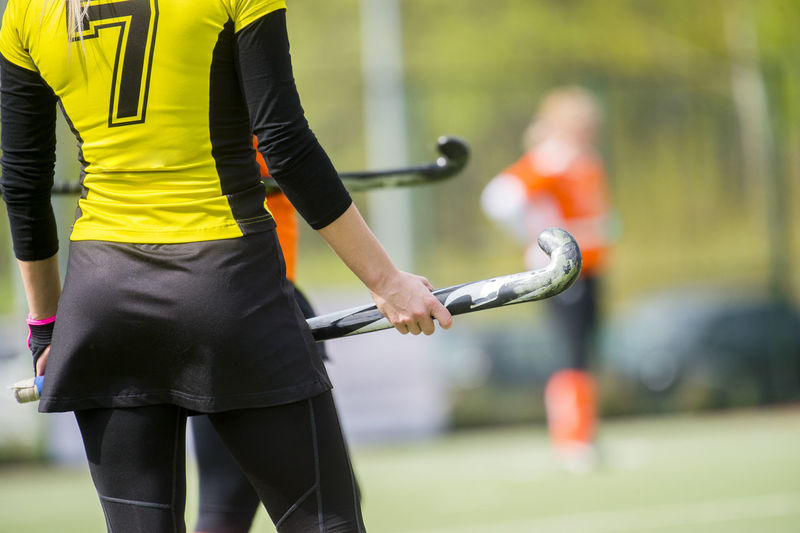 Rear view of woman holding hockey stick