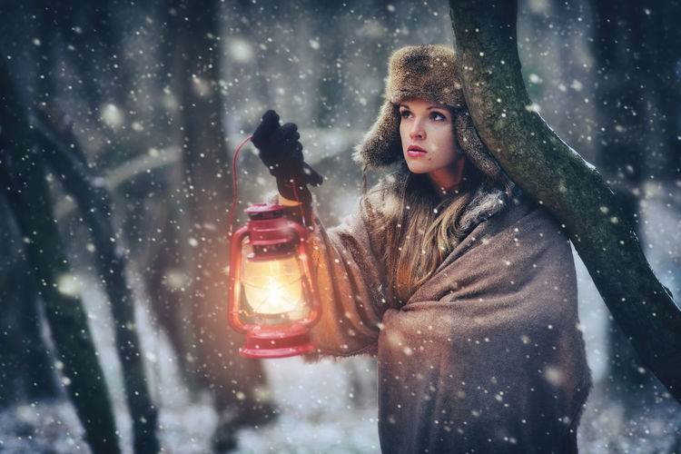 Lost young woman in the forest with a lantern at snowstorm Alone Caucasian Cold Dark Fabulous Fear Fine Art Photography Forest Frozen Hat Lantern Light Lost Mysterious Night Outdoors People Portrait Portrait Of A Woman Snow Snowflake Snowing Winter Young Adult Young Women EyeEmNewHere The Portraitist - 2017 EyeEm Awards EyeEm Selects Been There. The Week On EyeEm Visual Creativity