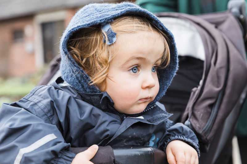 Close-Up Of Cute Baby Girl Wearing Warm Clothing Looking Away