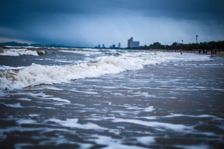 Waves rushing on shore against sky