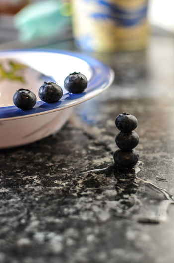 Blueberries by bowl on marble