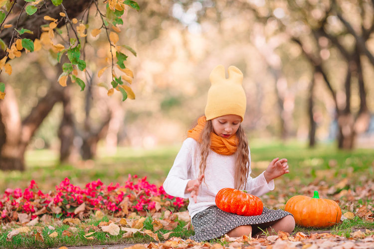 Full length of a girl with pumpkins in garden