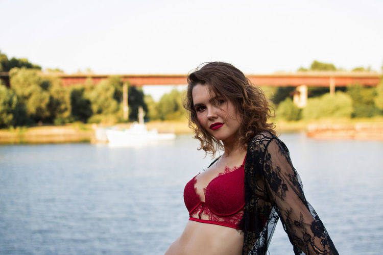 Portrait of beautiful woman against water