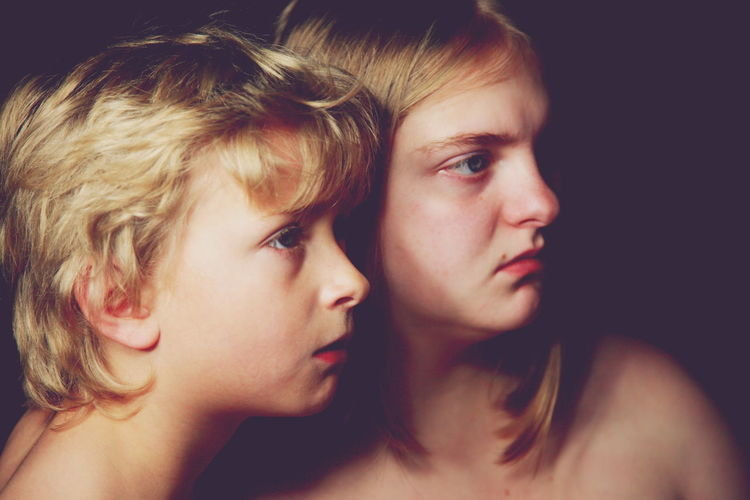 Close-Up Of Shirtless Brother And Sister Looking Away