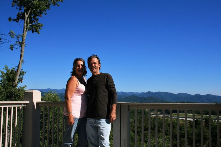 Portrait of smiling couple standing at balcony against clear blue sky