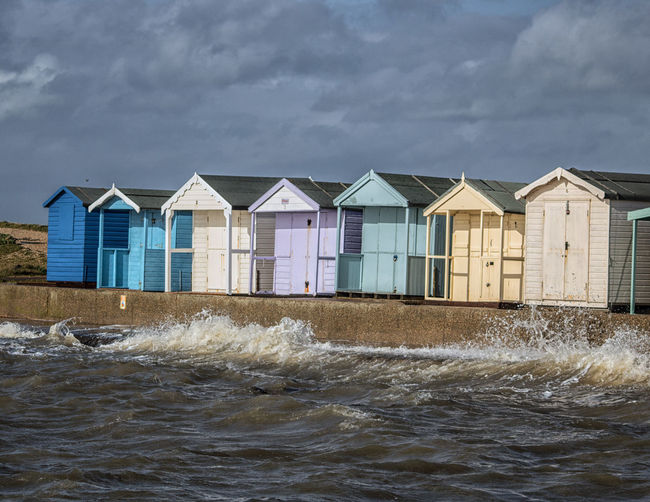 Beach huts in row by sea against cloudy sky