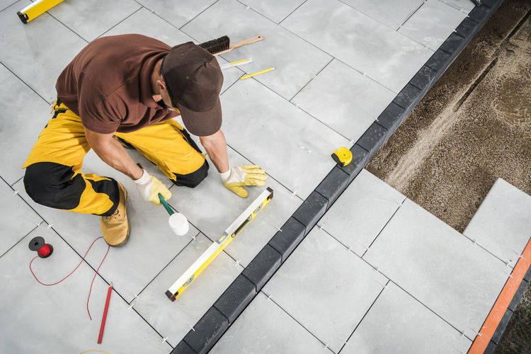 High angle view of man with umbrella on tiled floor