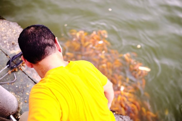 Street colour...giving fish eat EyeEm Selects Water Real People Rear View Yellow One Person Leisure Activity Lifestyles Outdoors Focus On Foreground Day Nature Men People Swimming