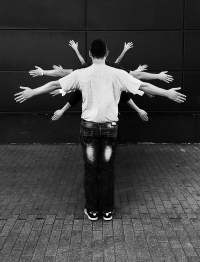 Rear view of young man standing with arms outstretched