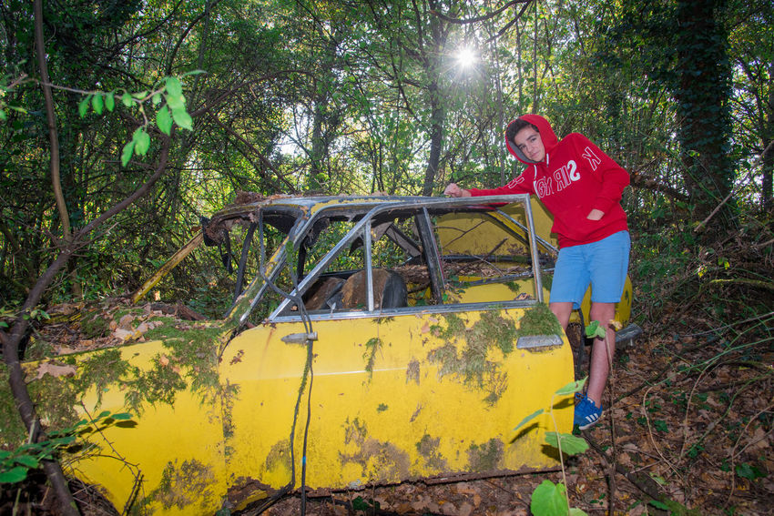 Old Real People One Person One Boy Only Teenage Boys Teen Teenager Nature Vintage Forest Abandoned Accident Tree Rusty Weathered Vehicle Car Retro Styled Plant Full Length Casual Clothing Standing Day Leisure Activity Land Front View Men Lifestyles Growth Transportation Yellow Outdoors