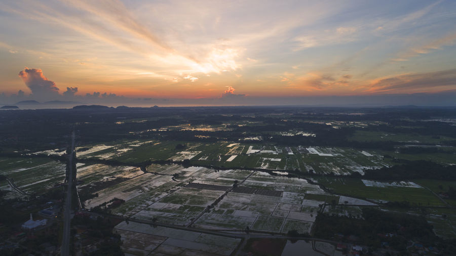 A view of rice field plantation area during sunrise. Agriculture Architecture Beauty In Nature Building Exterior Built Structure City Cityscape Cloud - Sky Day Field Landscape Nature Nature, Landscape, Green, View, Rural, Farm, Agriculture, Field, High, Grass, Environment, Summer, Land, Aerial, Air, Beautiful, Sky, Food, Grow, Top, Plant, Harvest, Pattern, Earth, Ground, Natural, Survey, Angle, Flying, Above, Background, Country, Terr No People Outdoors Patchwork Landscape Rural Scene Scenics Sky Sunset Tranquil Scene Tranquility