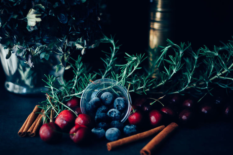 Close-up of fruits with rosemary and cinnamons on table