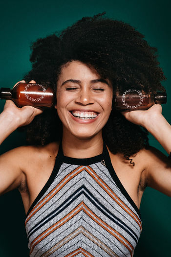 Green Advertisement Advertising Beautiful Woman Teeth Real People Lifestyles Curly Hair Leisure Activity Hairstyle Waist Up Young Women Black Hair Holding Hair Indoors  Happiness Looking At Camera Young Adult Portrait One Person Front View Smiling Indoors  Toothy Smile Frizzy Moments Of Happiness