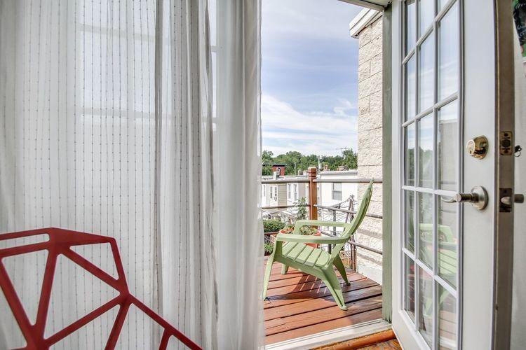 Adirondack chair in balcony seen from open doorway at home