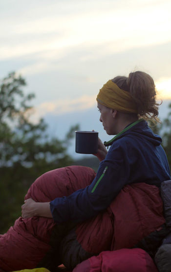 caucasian female hiker drinking beverage from cup while wild camping outdoors Backpacking Camping Coffee Expedition Hiking Hydration Nature Tea Travel Trekking Woman Activity Caucasian Clothing Communication Connection Cozy Drinking Female Girl Holding Leisure Activity Lifestyles Mobile Phone Nature One Person Outdoors Outside People Photographing Photography Themes Portable Information Device Portrait Real People Relaxation Sitting Sleeping Bag Smart Phone Technology Three Quarter Length Warm Clothing Wireless Technology