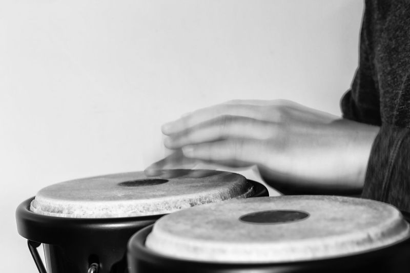 Blurred Motion Of Person Playing Drums Against Wall