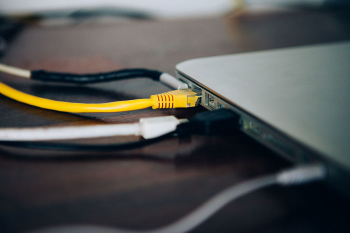 Close up yellow LAN cable is connecting internet to laptop Cable Close-up Communication Computer Computer Cable Computer Equipment Computer Network Connection Electrical Component Electricity  Indoors  Internet Network Connection Plug Network Server No People Phone Cord Router Selective Focus Still Life Table Technology Two Objects Wireless Technology Yellow