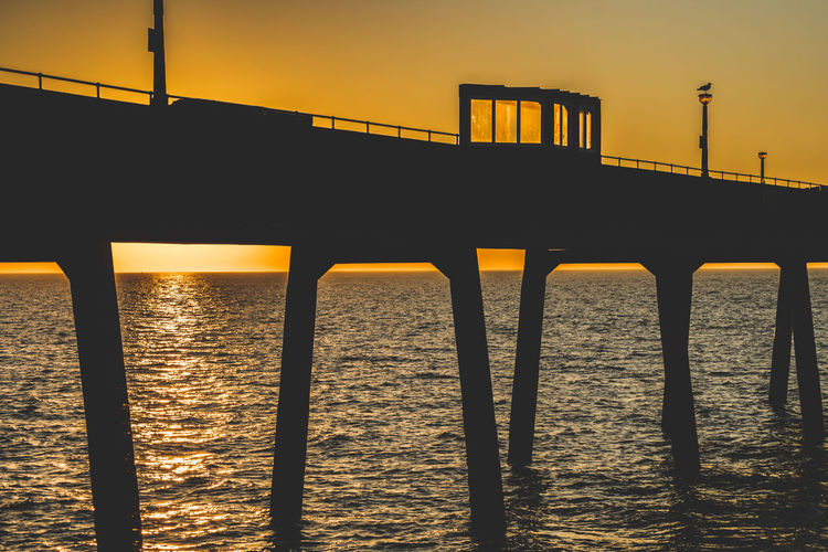 Silhouette bridge over sea against clear sky during sunset