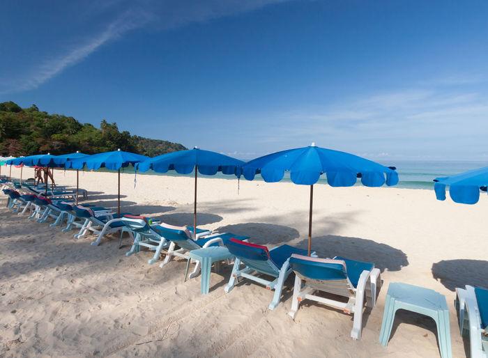 Chairs on beach against blue sky