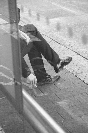 Man Smoking While Sitting At Sidewalk Seen Through Glass