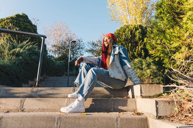 Low angle portrait of young woman sitting on steps against sky