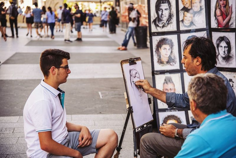 Piazza Duomo Street Artist Adult Architecture Casual Clothing City Communication Day Group Of People Incidental People Leisure Activity Lifestyles Looking Males  Men Mialano People Real People Sitting Technology Three Quarter Length Walking Young Adult Young Men